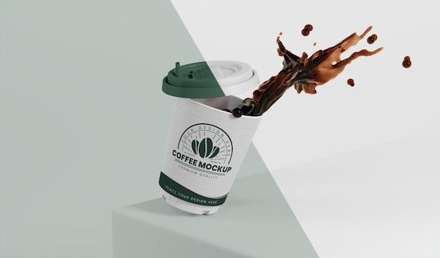 Zusammensetzung der kaffeetasse aus papier mit kaffeespritzer