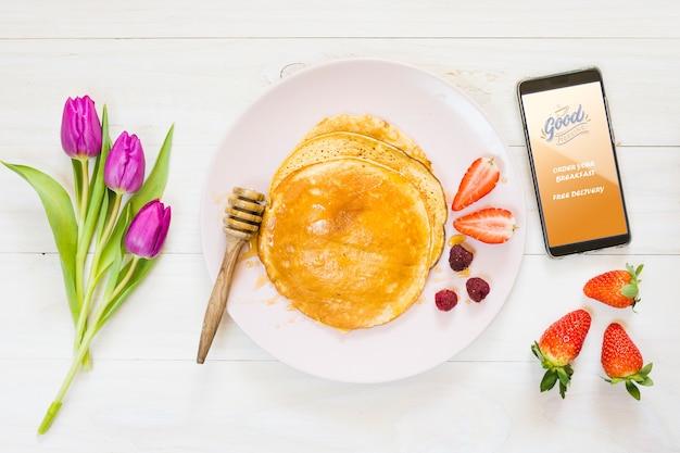 Zusammenstellung von frühstückspfannkuchen nahe bei smartphone