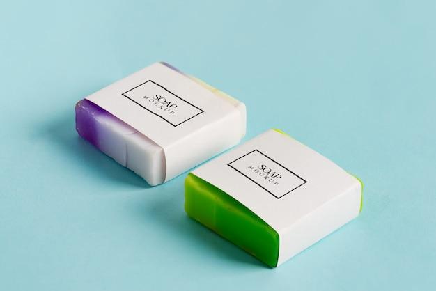 Zwei handgemachte seifenverpackungsbox-modellpaket mit bunter stückseife lokalisiert auf blauem hintergrund