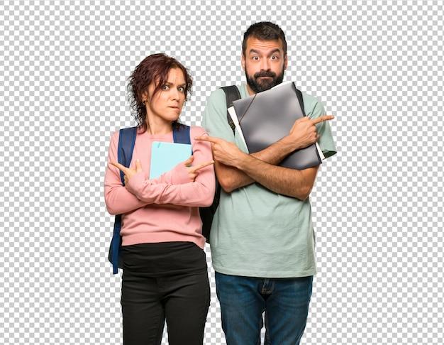 Zwei studenten mit rucksäcken und büchern, die auf die seitenteile zeigen, die zweifel haben