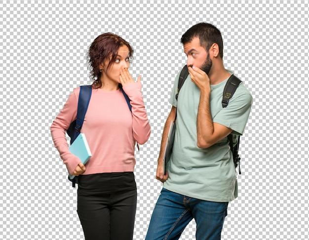 Zwei studenten mit rucksäcken und büchern, die den mund mit den händen bedecken, weil sie etwas unangemessenes gesagt haben