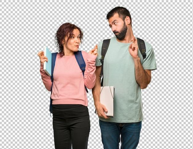 Zwei studenten mit rucksäcken und büchern, die die daumen drücken und das beste wünschen