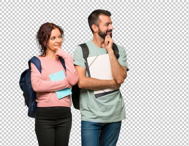 Zwei studenten mit rucksäcken und büchern, die mit der hand am kinn zur seite schauen