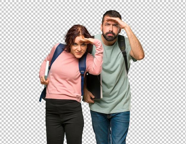 Zwei studenten mit rucksäcken und büchern, die weit weg mit der hand schauen, um etwas zu schauen