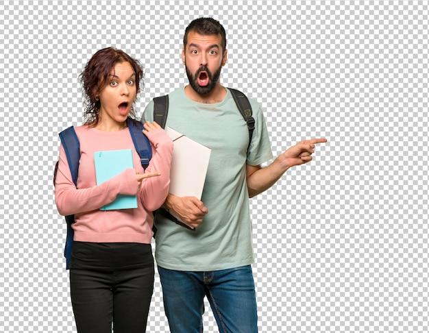 Zwei studenten mit rucksäcken und büchern finger auf die seite mit einem überraschten gesicht zeigend