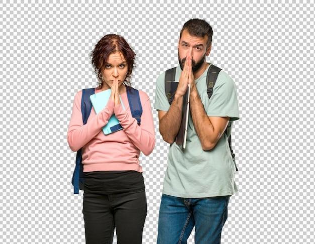 Zwei studenten mit rucksäcken und büchern halten handflächen zusammen. person bittet um etwas
