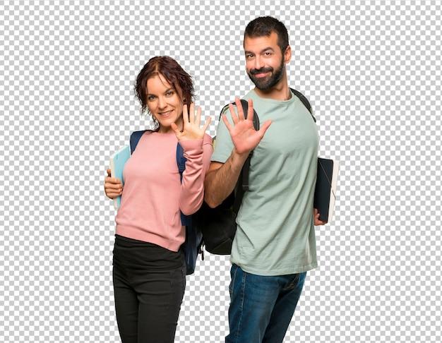 Zwei studenten mit rucksäcken und büchern zählen fünf mit den fingern