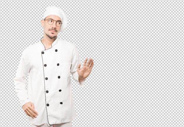 Zweifelhafter junger koch, der eine geste der ruhe tut