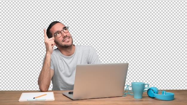 Zweifelhafter junger mann, der an seinem schreibtisch sitzt und oben zeigt