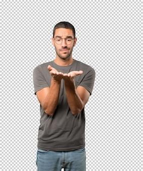 Zweifelhafter junger mann, der etwas mit seiner hand hält