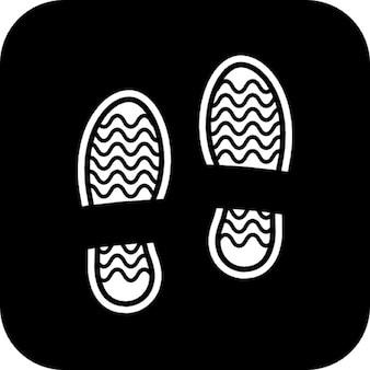 Impronte di scarpe su uno sfondo quadrato nero