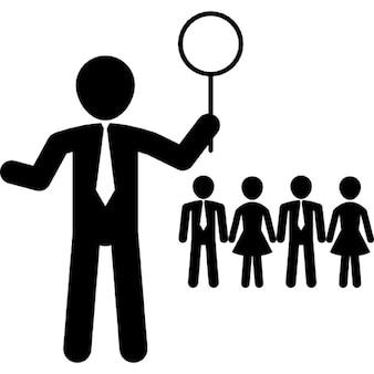 Leader di affari che tiene lente di ingrandimento con altri lavoratori su sfondo