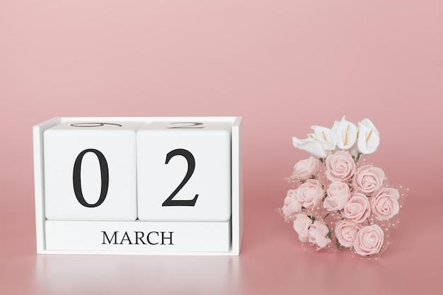 02 mars. jour 2 du mois. cube de calendrier sur rose moderne