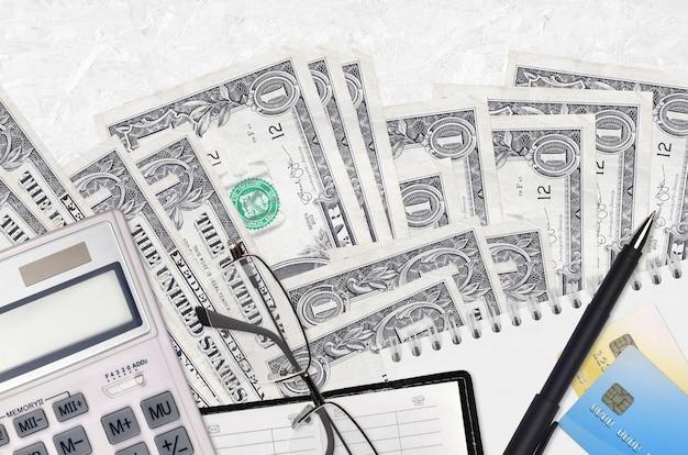 1 billets en dollars américains et calculatrice avec lunettes et stylo