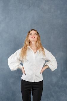 1 jeune femme blonde blanche dans un chemisier blanc lève les yeux sur une surface grise