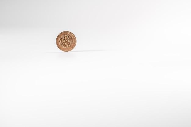 1 pièce de monnaie britannique livre tombant sur fond blanc, isolé