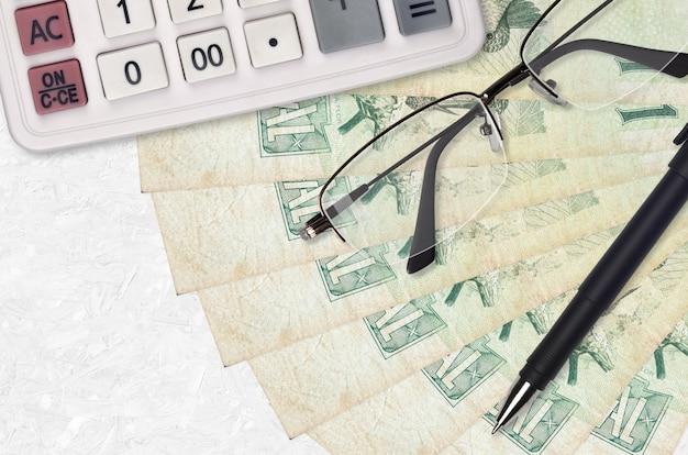 1 ventilateur et calculatrice de factures en real brésilien avec lunettes et stylo. prêt commercial ou concept de saison de paiement des impôts
