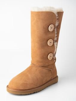 10.04.2021 russie, moscou. gros plan de la botte ugg en peau de mouton haute sur fond blanc. chaussures chaudes, tourné en studio