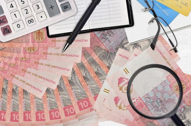 10 factures de hryvnias ukrainiennes et calculatrice avec lunettes et stylo