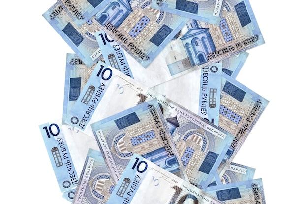 10 factures de roubles biélorusses volant vers le bas isolé sur blanc. de nombreux billets tombant avec espace copie blanche sur le côté gauche et droit