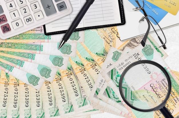 10 factures de roupies sri-lankaises et calculatrice avec lunettes et stylo