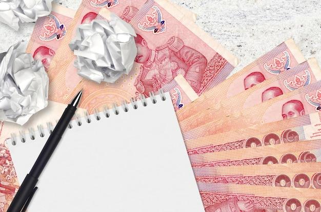 100 billets de baht thaïlandais et boules de papier froissé avec bloc-notes vierge
