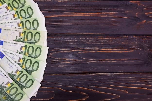 100 billets en euros sur fond de bois avec espace de copie. notion financière.