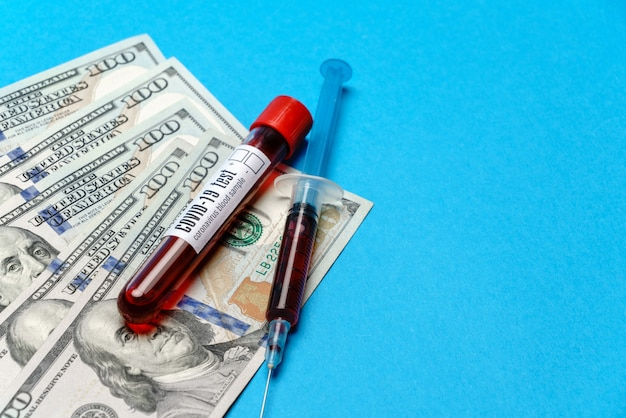 100 dollars américains et échantillon de sang en tube à essai sur bleu