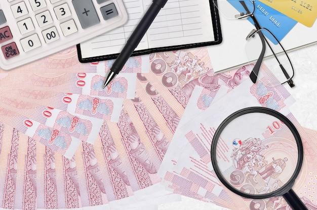 100 factures de baht thaïlandais et calculatrice avec lunettes et stylo