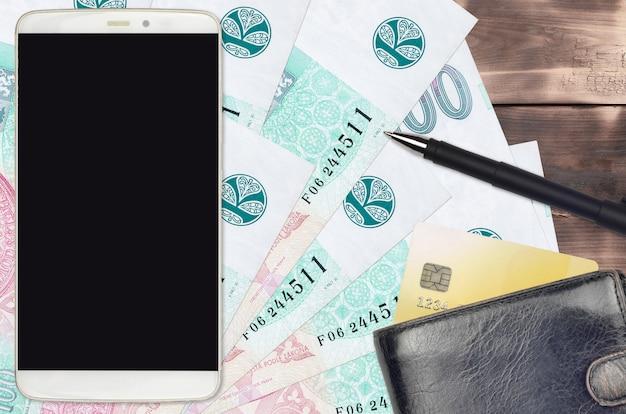 100 factures de couronnes tchèques et smartphone avec sac à main et carte de crédit. concept de paiements électroniques ou de commerce électronique. achats en ligne et affaires avec des appareils portables