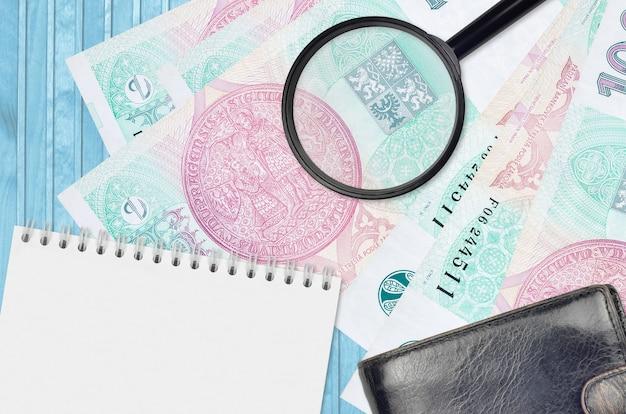 100 factures de korun tchèque et loupe avec sac à main noir et bloc-notes