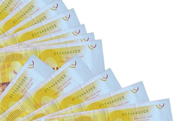 100 nouveaux billets de shekels israéliens se trouvent isolés empilés en éventail de près. concept de temps de paie ou opérations financières