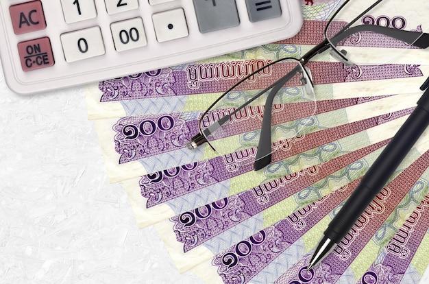 100 riels cambodgiens fan et calculatrice avec lunettes et stylo. prêt commercial ou concept de saison de paiement de l'impôt. planification financière
