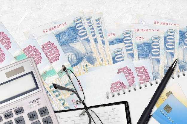 1000 factures en forint hongrois et calculatrice avec lunettes et stylo. concept de saison de paiement des impôts ou solutions d'investissement. planification financière ou paperasse comptable