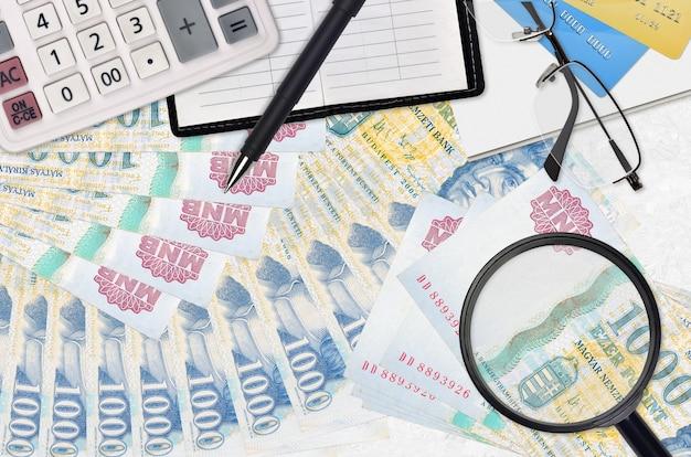1000 factures en forint hongrois et calculatrice avec lunettes et stylo.