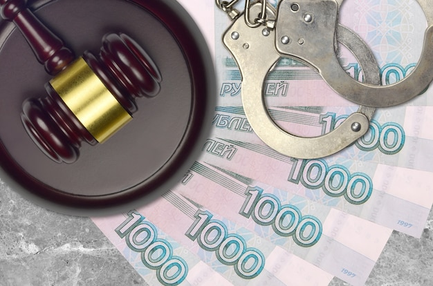 1000 roubles russes factures et juge marteau avec des menottes de police sur le bureau du tribunal. concept de procès judiciaire ou de corruption. évasion fiscale ou évasion fiscale
