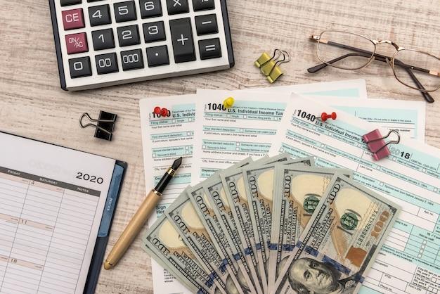 1040 formulaire d'impôt avec argent et calculatrice. concept fiscal.