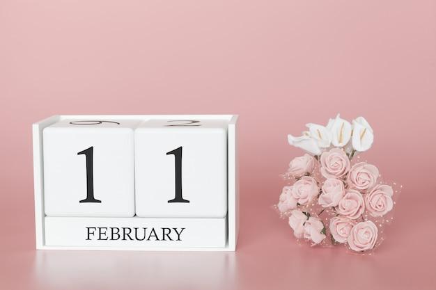 11 février. jour 11 du mois. cube de calendrier sur fond rose moderne, concept de commerce et événement important.