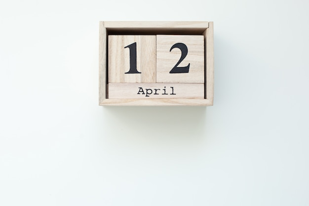 12 avril calendrier de bloc en bois de pâques sur un mur blanc isolé. pâques. vue de dessus avec espace copie. pâques catholique. maison de décoration en bois rustique. carte de vacances de pâques printemps. vue de dessus. célébrer
