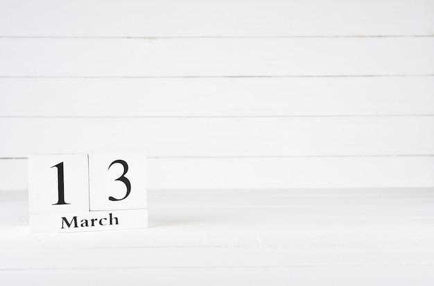 13 mars, jour 13 du mois, anniversaire, anniversaire, calendrier de bloc en bois sur un fond en bois blanc avec espace de copie du texte.