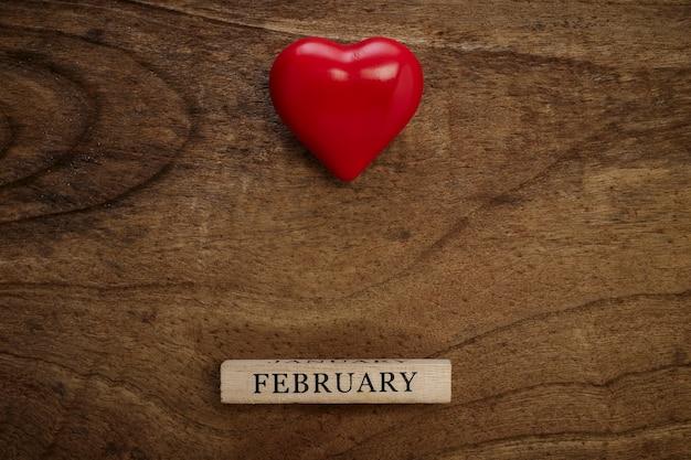 14 février sur bois avec un coeur rouge sur la texture en bois, vue du dessus