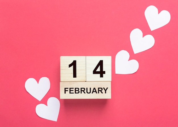 14 février sur calendrier en bois avec des coeurs rose pâle sur fond rouge.