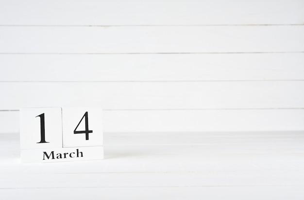 14 mars, jour 14 du mois, anniversaire, anniversaire, calendrier de bloc en bois sur un fond en bois blanc avec espace de copie du texte.
