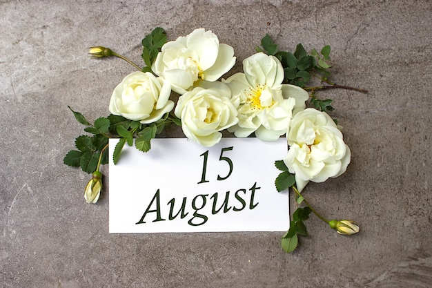 15 août. jour 15 du mois, date du calendrier. bordure de roses blanches sur fond gris pastel avec date du calendrier. mois d'été, concept de jour de l'année.