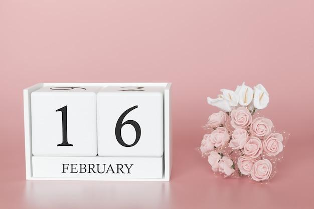 16 février. jour 16 du mois. cube de calendrier sur fond rose moderne, concept de commerce et événement important.