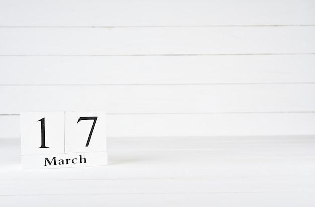 17 mars, jour 17 du mois, anniversaire, anniversaire, calendrier de bloc en bois sur un fond en bois blanc avec espace de copie du texte.