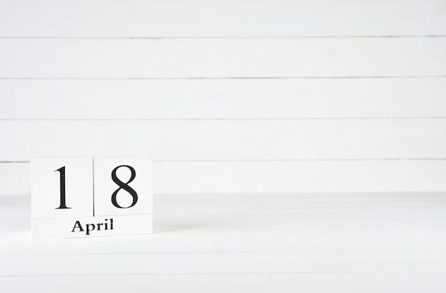 18 avril, jour 18 du mois, anniversaire, anniversaire, calendrier de bloc en bois sur un fond en bois blanc avec espace de copie du texte.