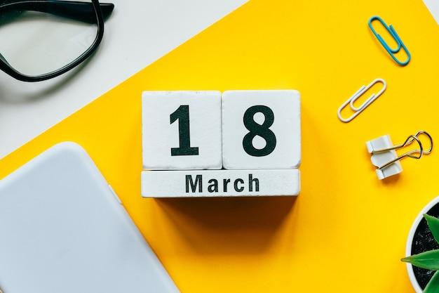 18 dix-huitième jour de mars sur le calendrier avec des fournitures de bureau