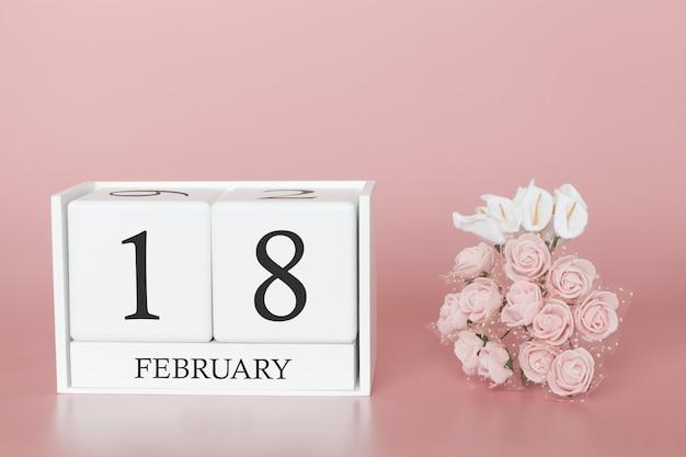 18 février. jour 18 du mois. cube de calendrier sur fond rose moderne, concept de commerce et événement important.
