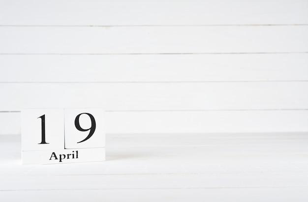 19 avril, jour 19 du mois, anniversaire, anniversaire, calendrier de bloc en bois sur un fond en bois blanc avec espace de copie du texte.
